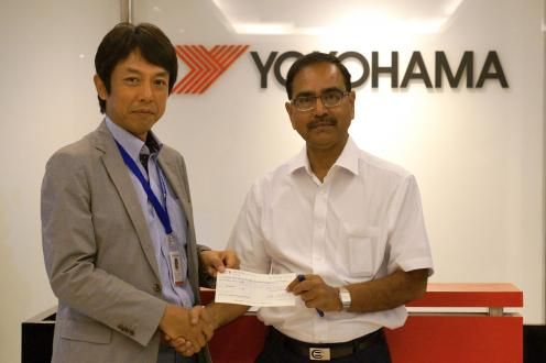 YIN President Satoshi Fujitsu presenting donation check to Indian Red Cross Deputy Secretary Mr. P.C. Partihari (right)