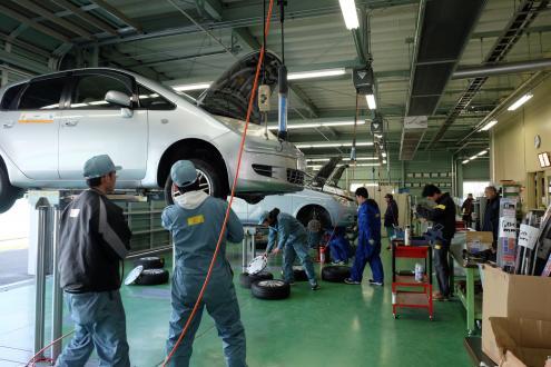 「春の学生整備プロジェクトでタイヤ交換を行う 石巻専修大学の学生」