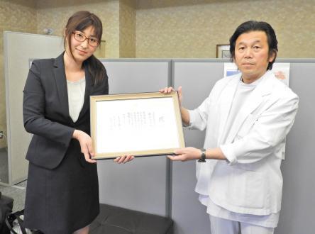 兵庫県立福祉のまちづくり研究所の陳隆明所長(右)から感謝状を受け取る