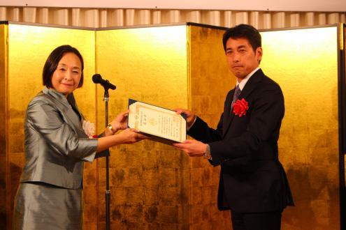 荒木田百合横浜副市長より認定証を授与されるハマゴムエイコムの近藤成俊代表取締役会長(右)